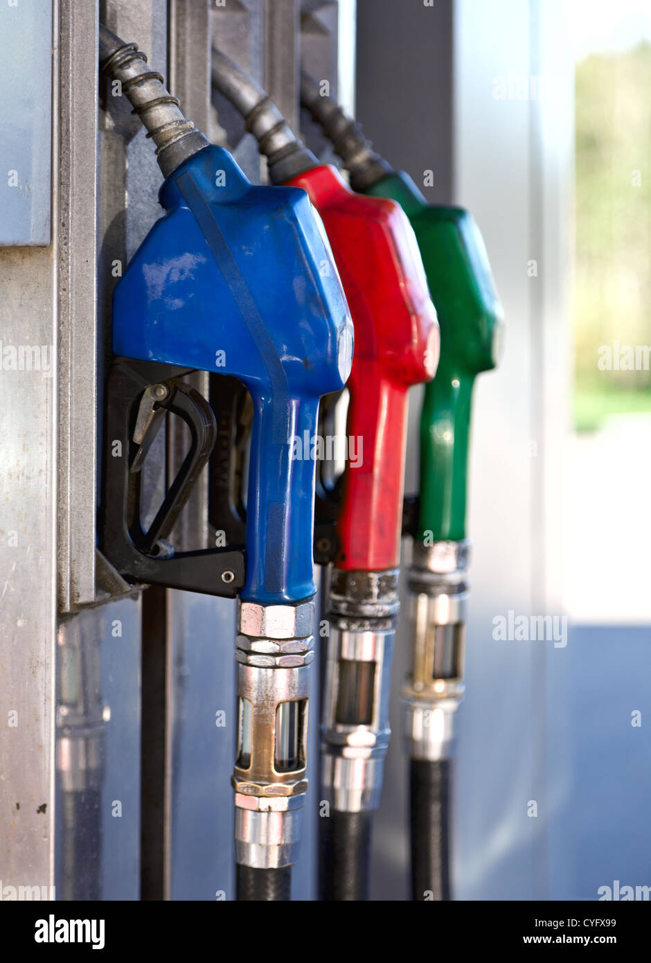 Three colorful pump nozzles at the gas station Stock Photo