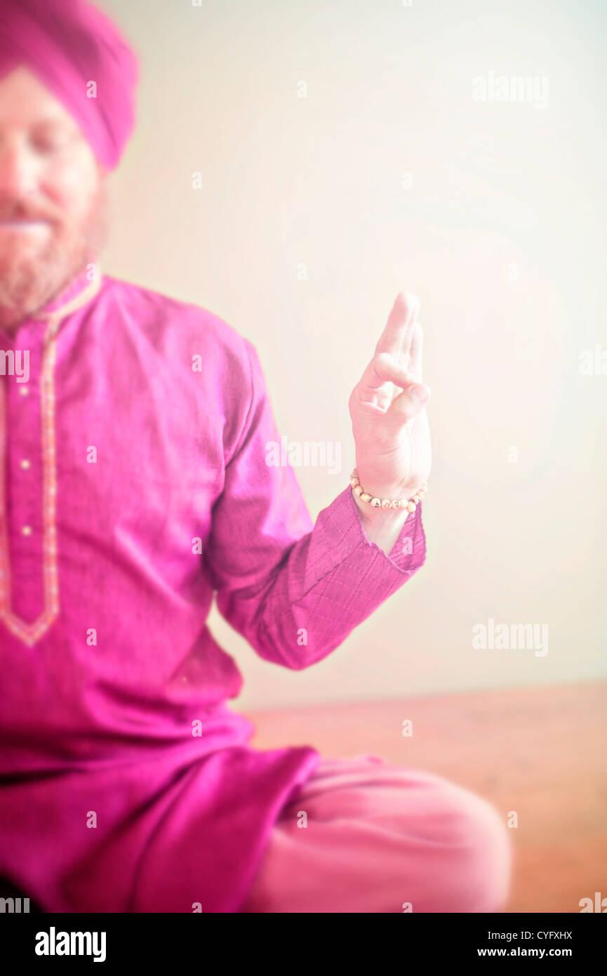 Guru in pink holding the sacred yoga mudra. - Stock Image