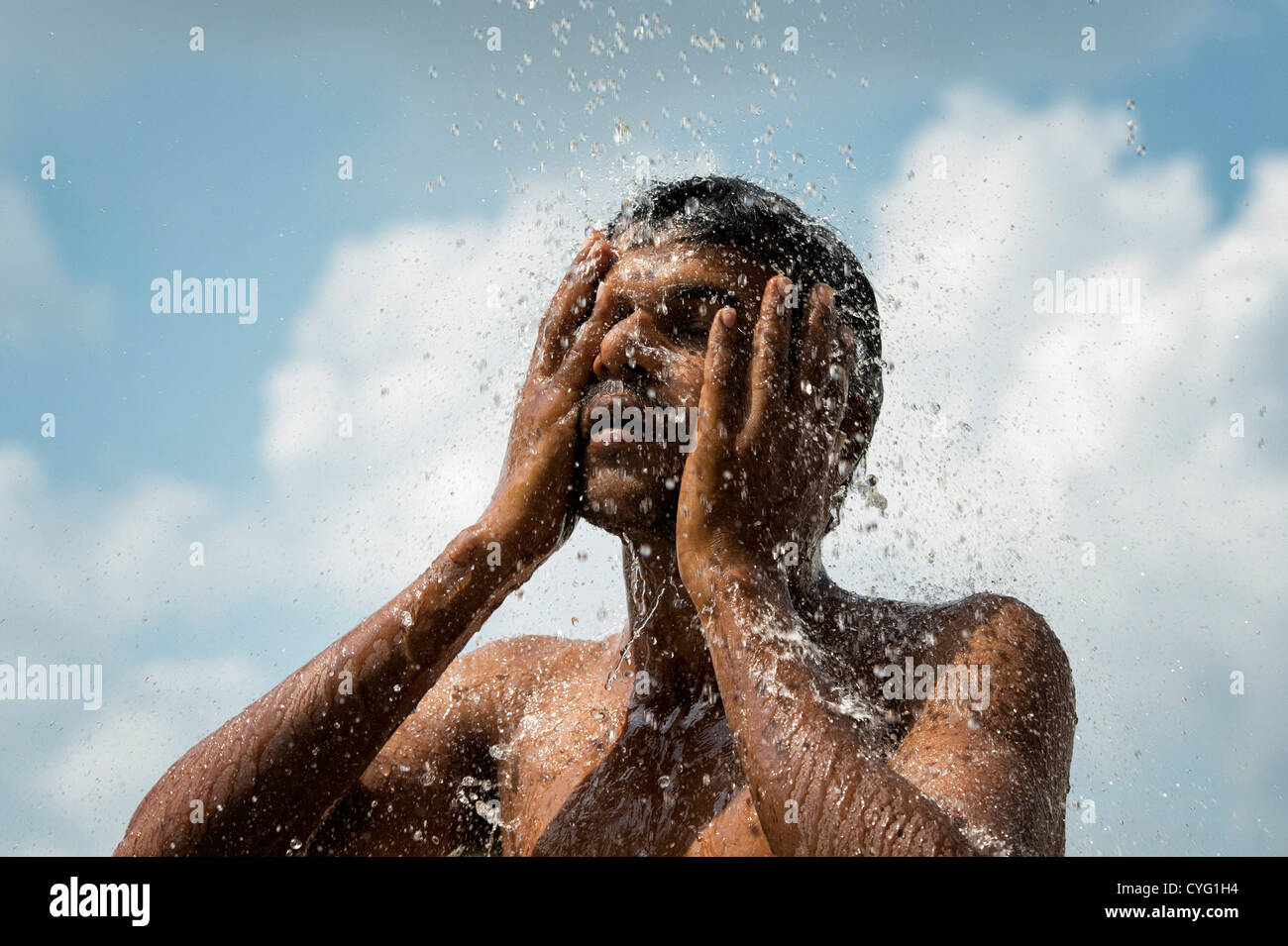 Indian man splashing water on his face against blue sky background. India - Stock Image