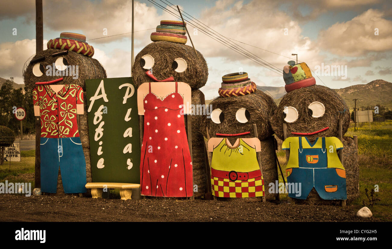 Farmyard characters made of hay bails at a farm stall - Stock Image