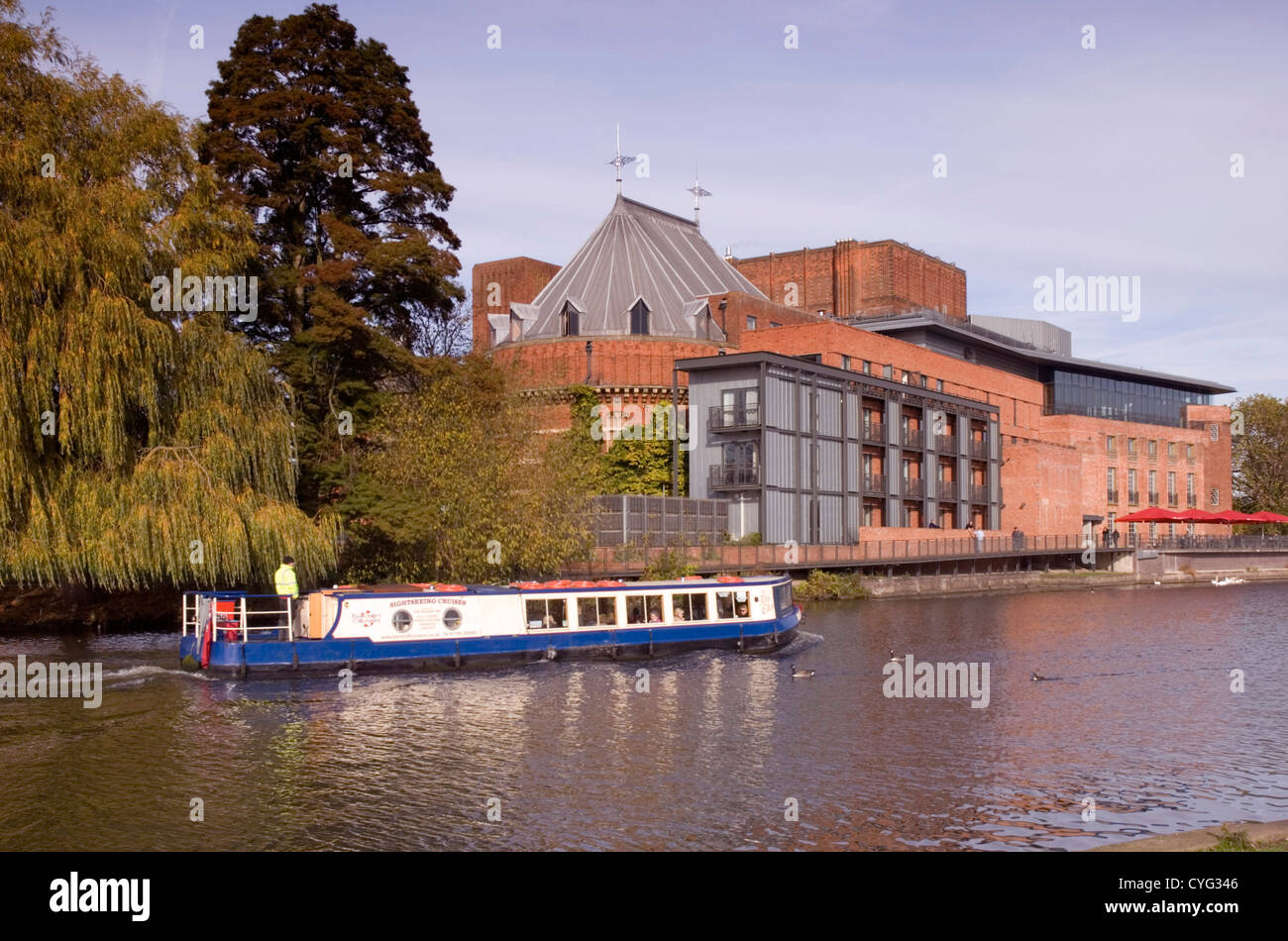 Warwickshire - Stratford upon Avon - tour boat passing RSC theatre on river Avon - autumn sunlight colours reflections - Stock Image