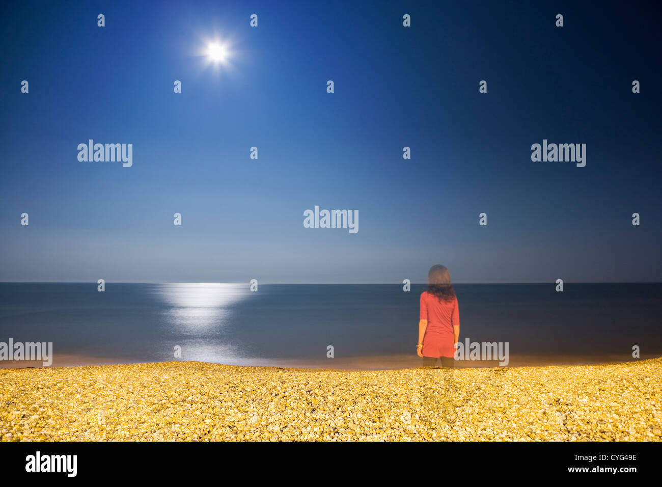 Woman standing on moonlit beach at night Stock Photo