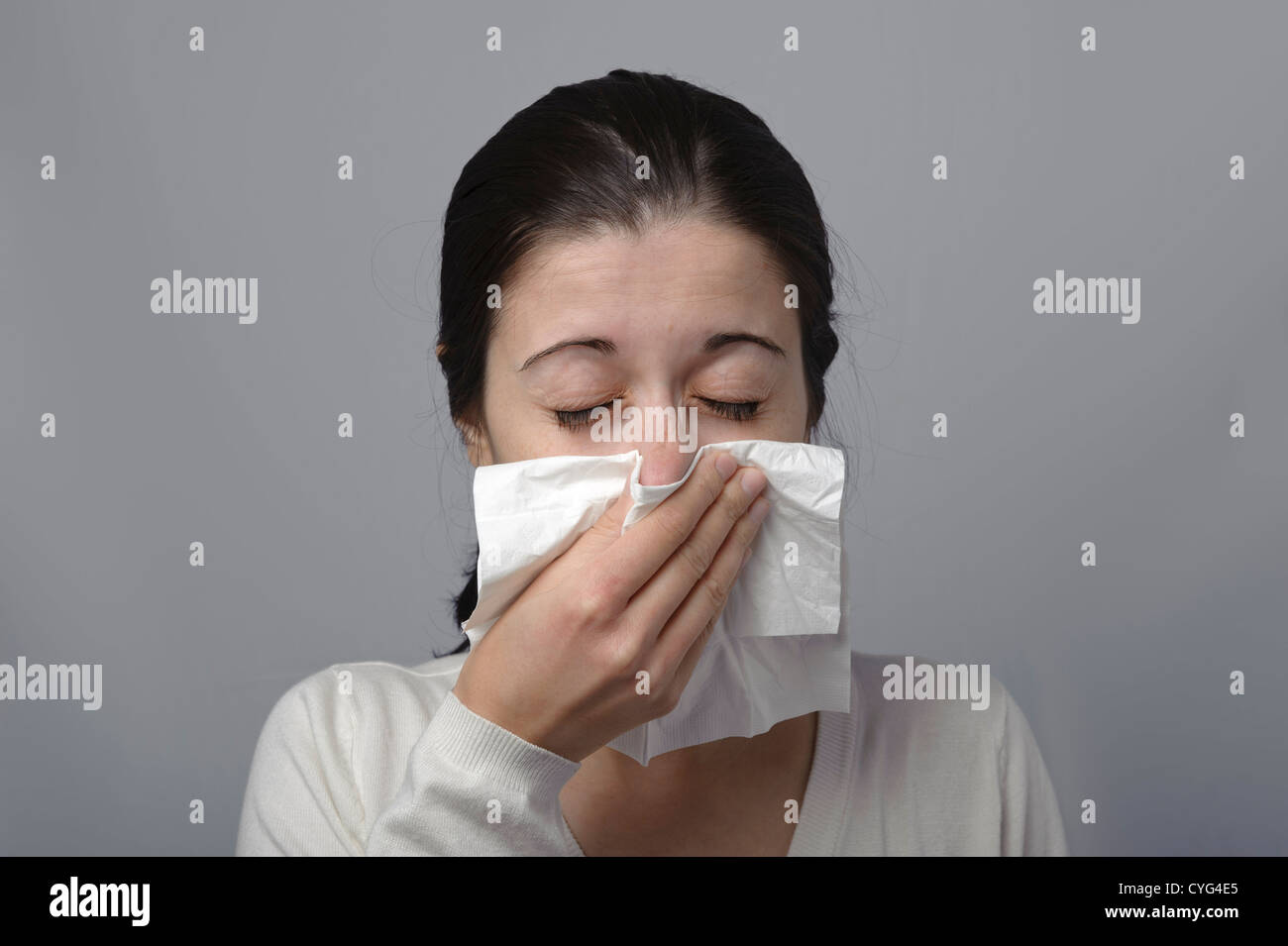 Young woman blowing her nose with tissue paper Stock Photo ...