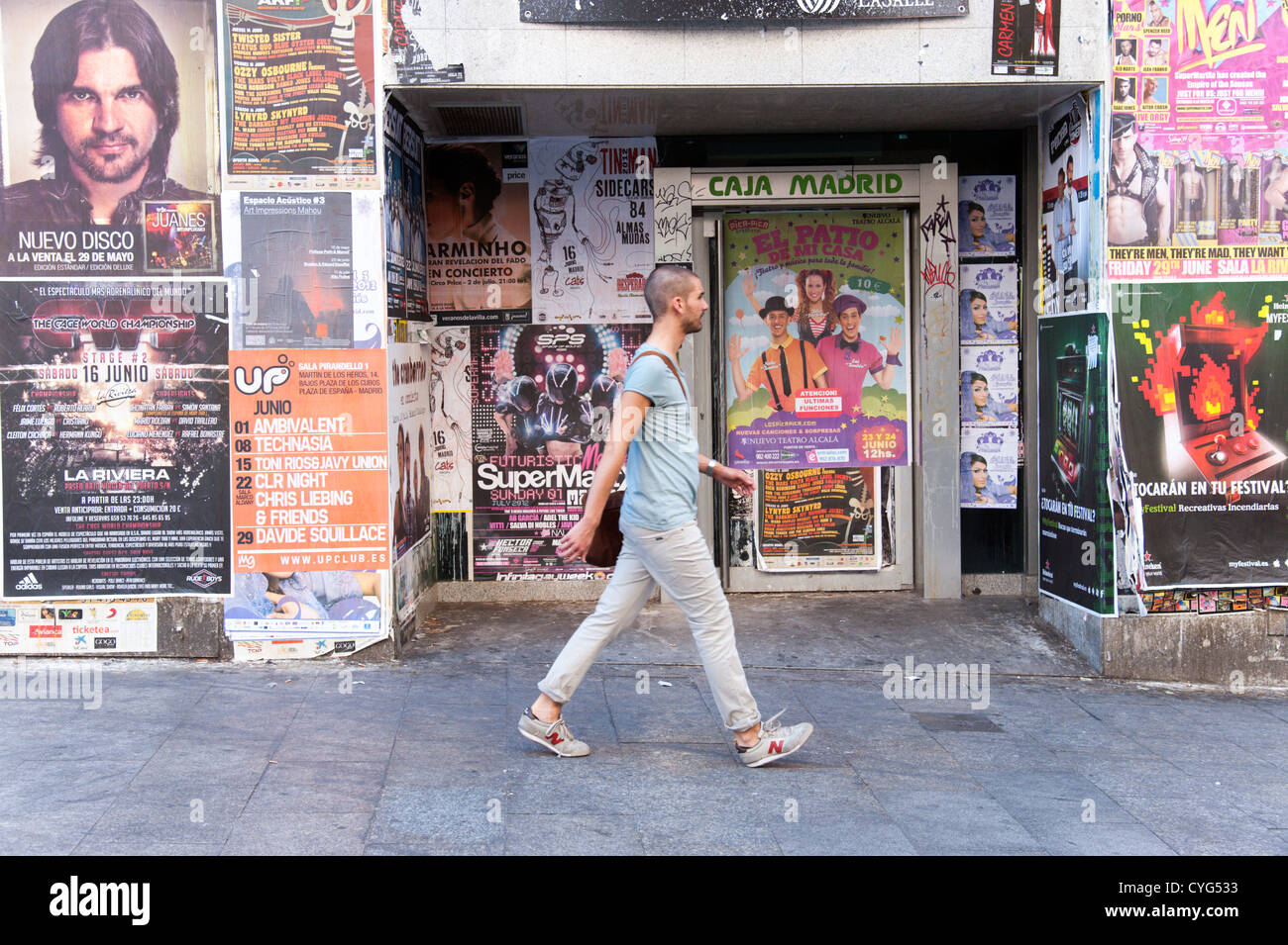 Young man walking past closed down bank branch of Caja Madrid, now part of Bankia, Madrid, Spain - Stock Image