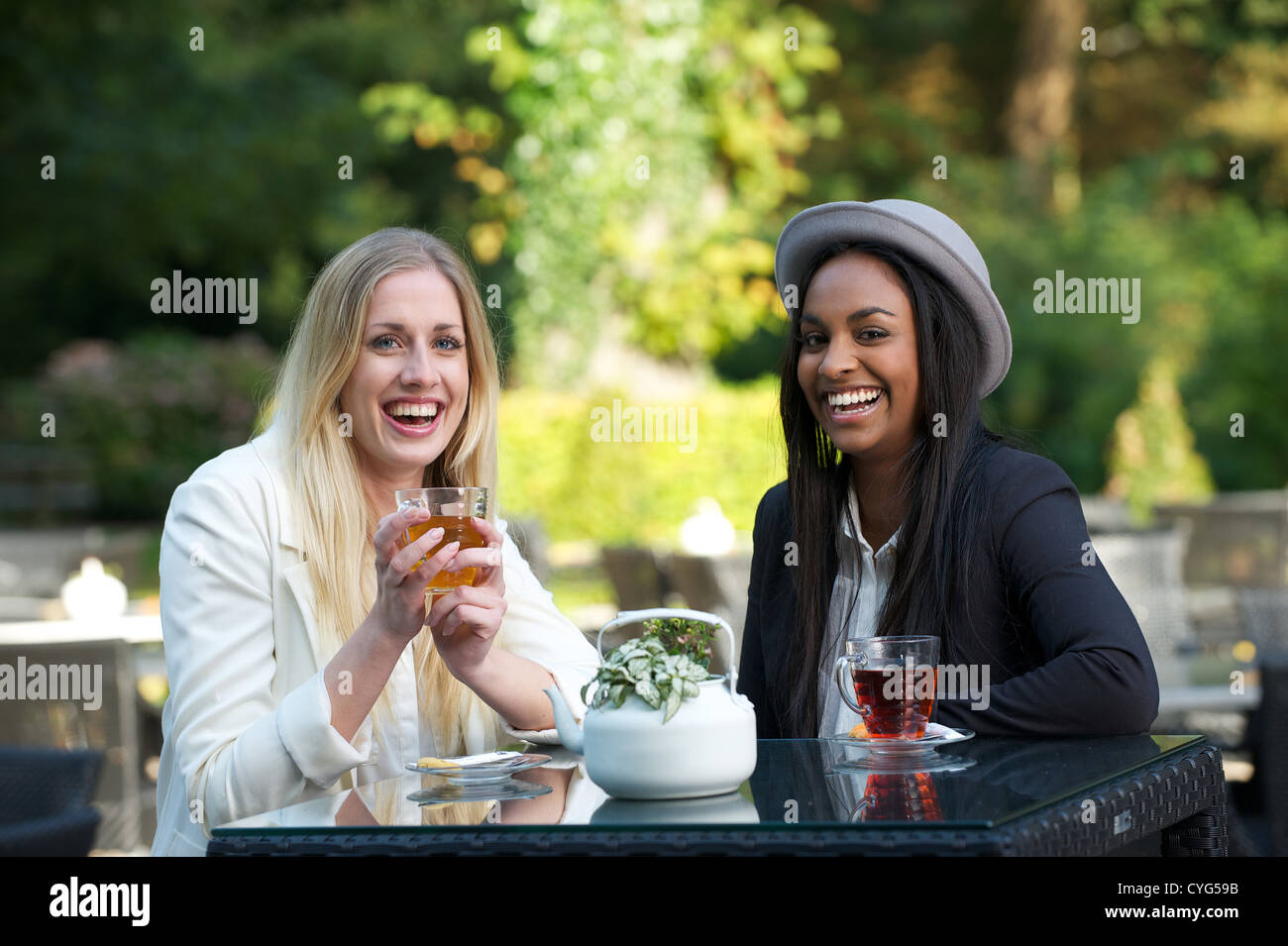 Two women friends laughing and having a good time while drinking tea outdoors - Stock Image