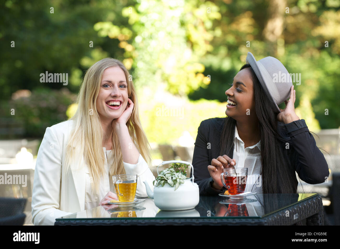 A couple of female friends sitting outdoors and smiling while drinking a cup of tea - Stock Image