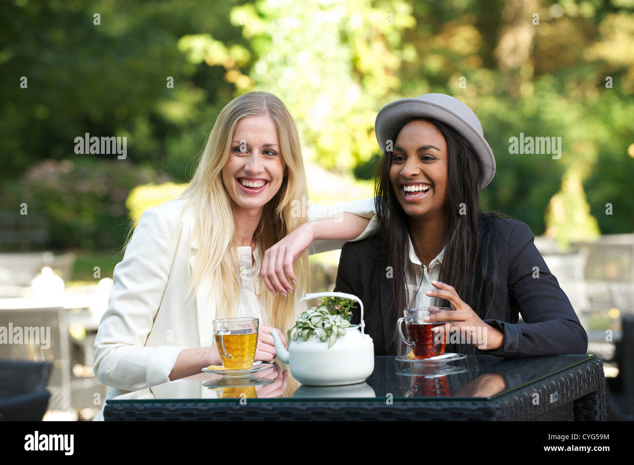 Two young women friends drinking tea outdoors and having a good time - Stock Image