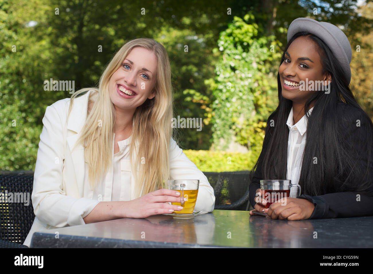 Portrait of two young women friends smiling and having a cup of tea outdoors - Stock Image