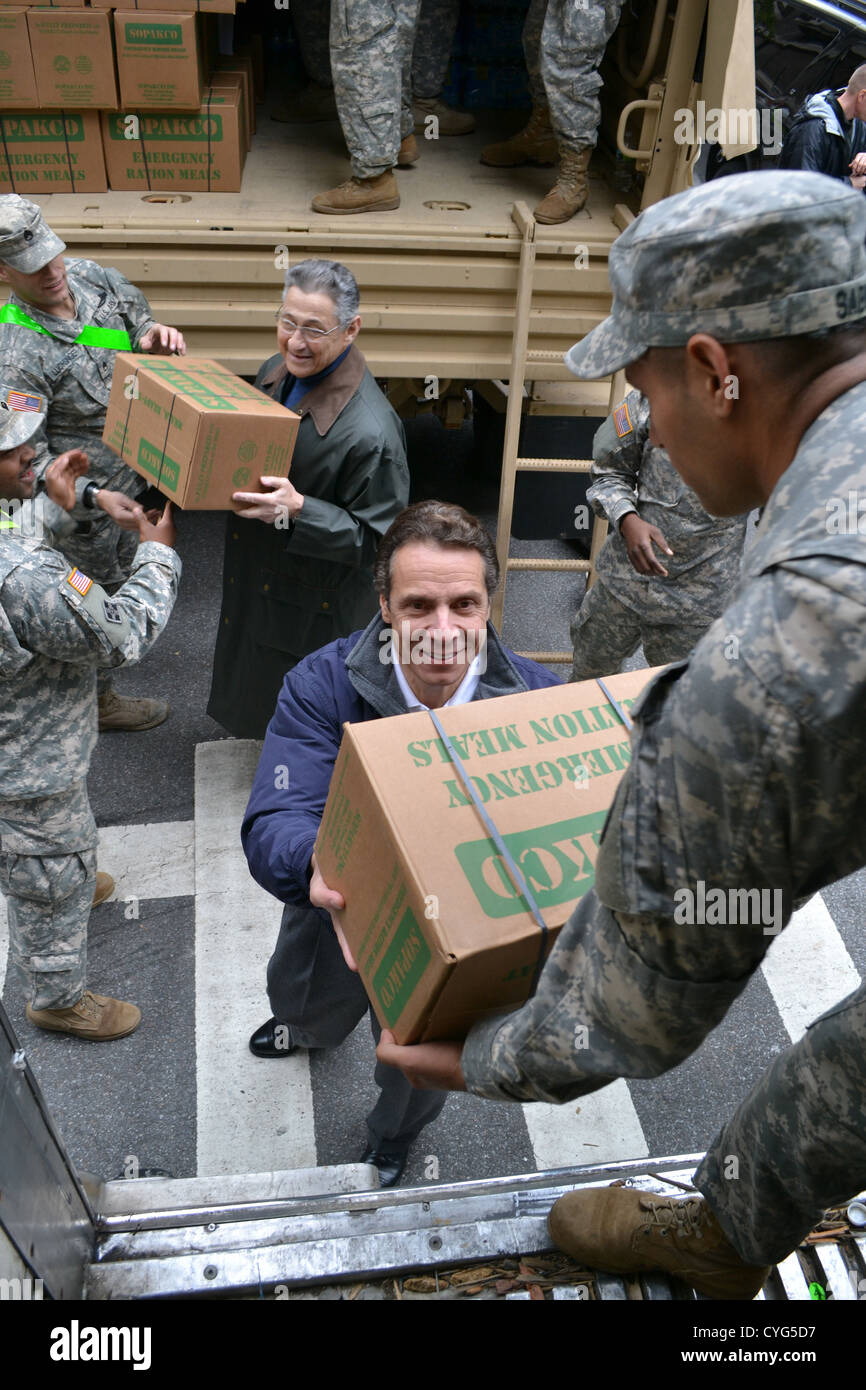 New York Governor Andrew Cuomo helps unload emergency supplies for Hurricane Sandy victims with New York Army National - Stock Image