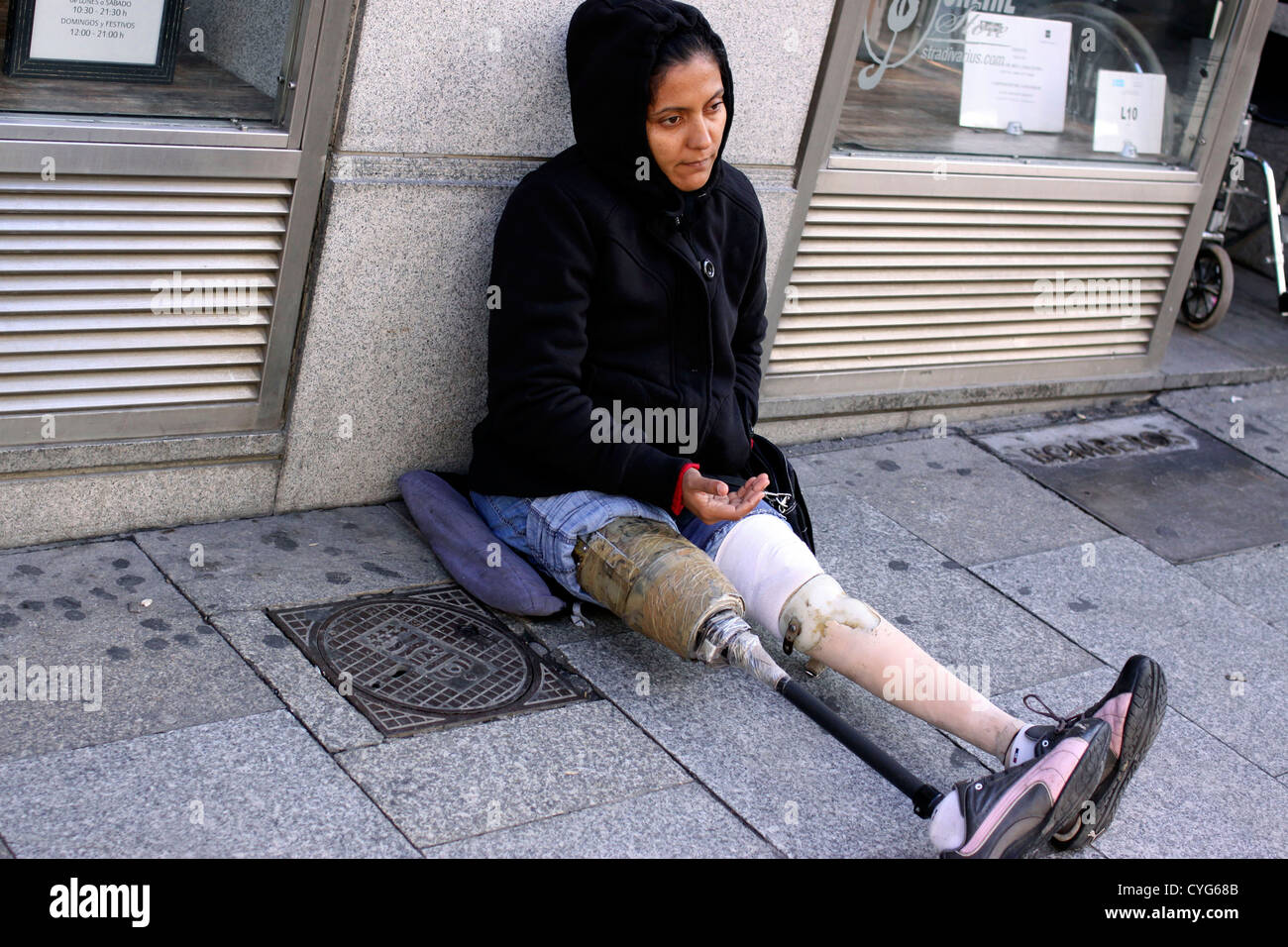 Woman with artificial legs begging on a street in Madrid - Stock Image