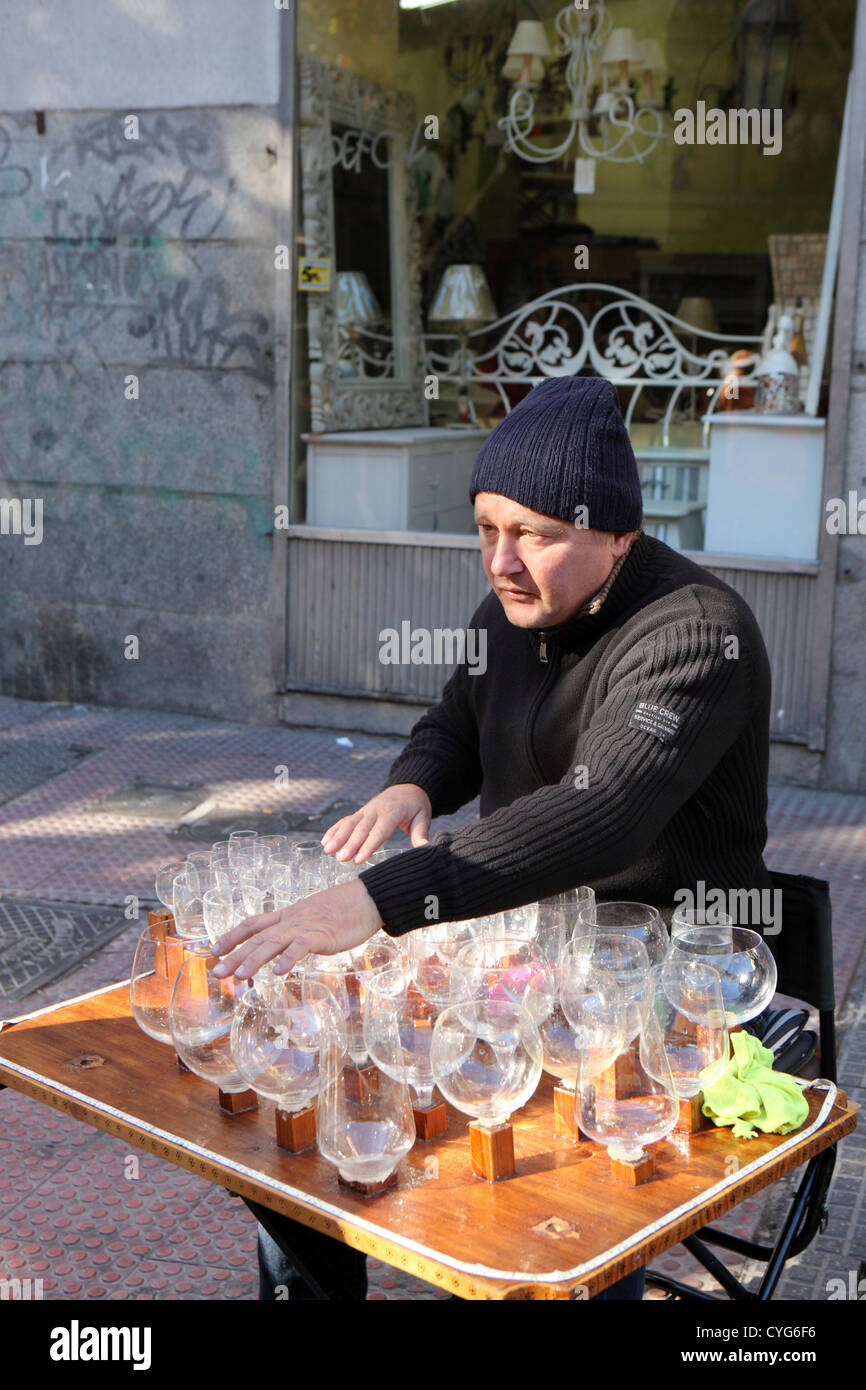 Middle aged man playing music on the Glass Harp wine glasses with amounts of water El rastro street market Madrid - Stock Image