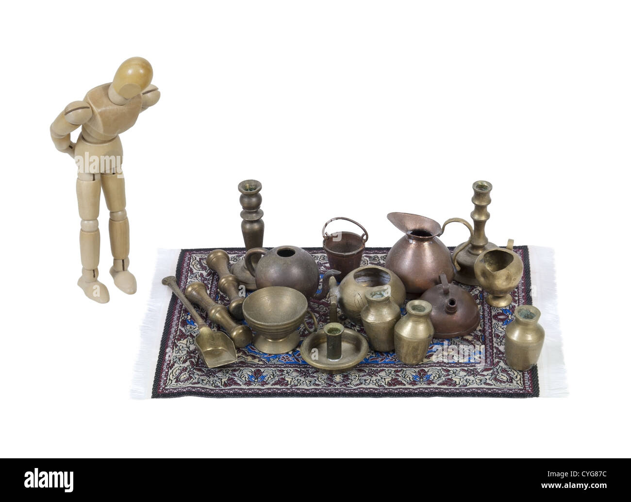 Shopping through a variety of different junk items on an intricate rug - path included - Stock Image
