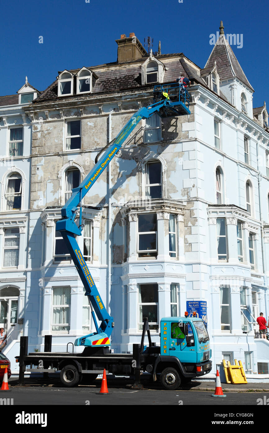 Workmen using a cherry picker to repair gutters on property in the U.K. - Stock Image