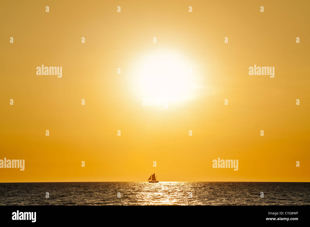 Sailboat at the horizon in front of the setting sun. - Stock Image