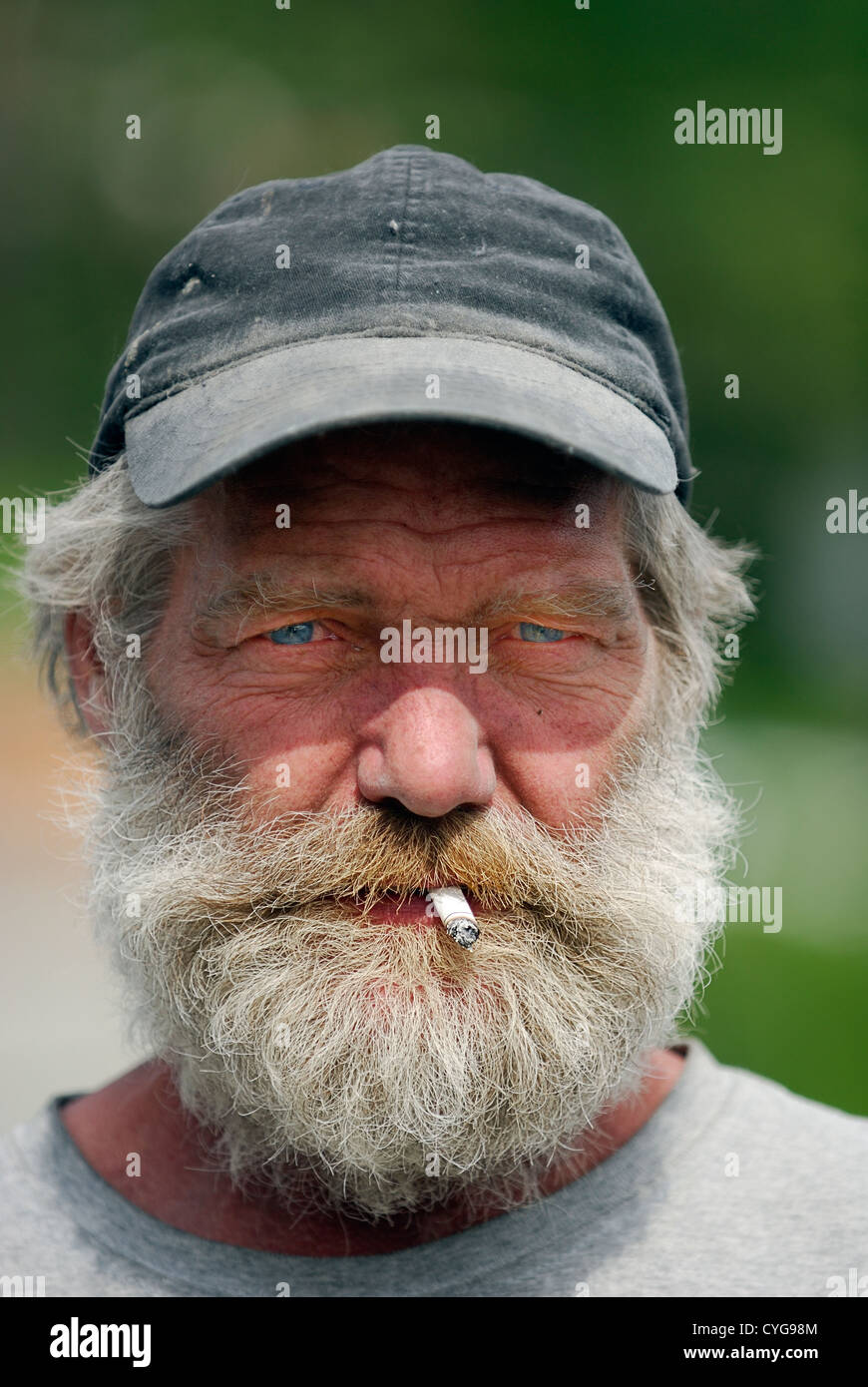 61429715ce8 Portrait of an old man with a grey beard wearing a cap smoking. - Stock