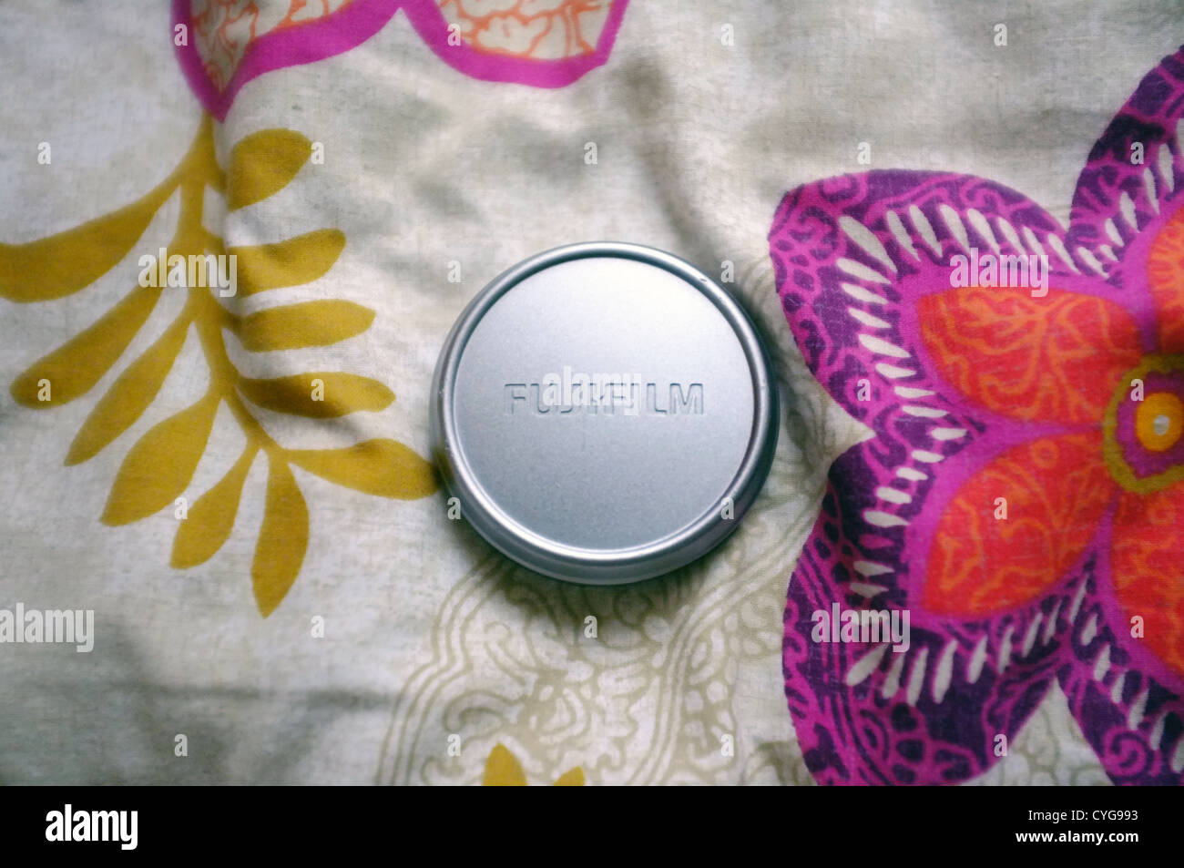 Fujifilm silver lens cap on a patterned background. - Stock Image