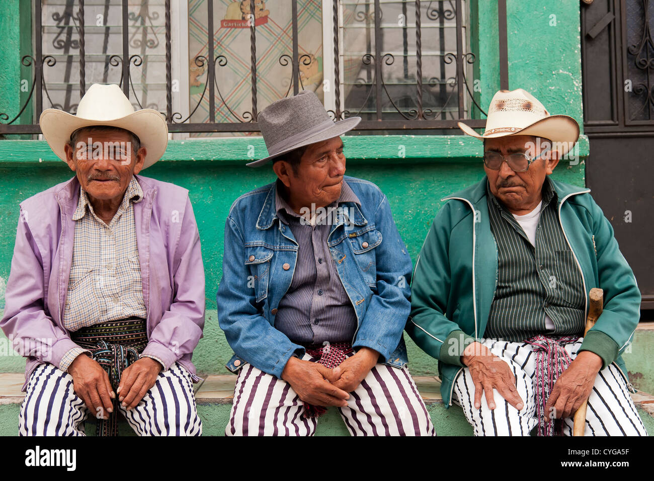Three men await the worship of Maximón, a folk saint, and dress appropriately during Easter in Santiago Atitlan, - Stock Image