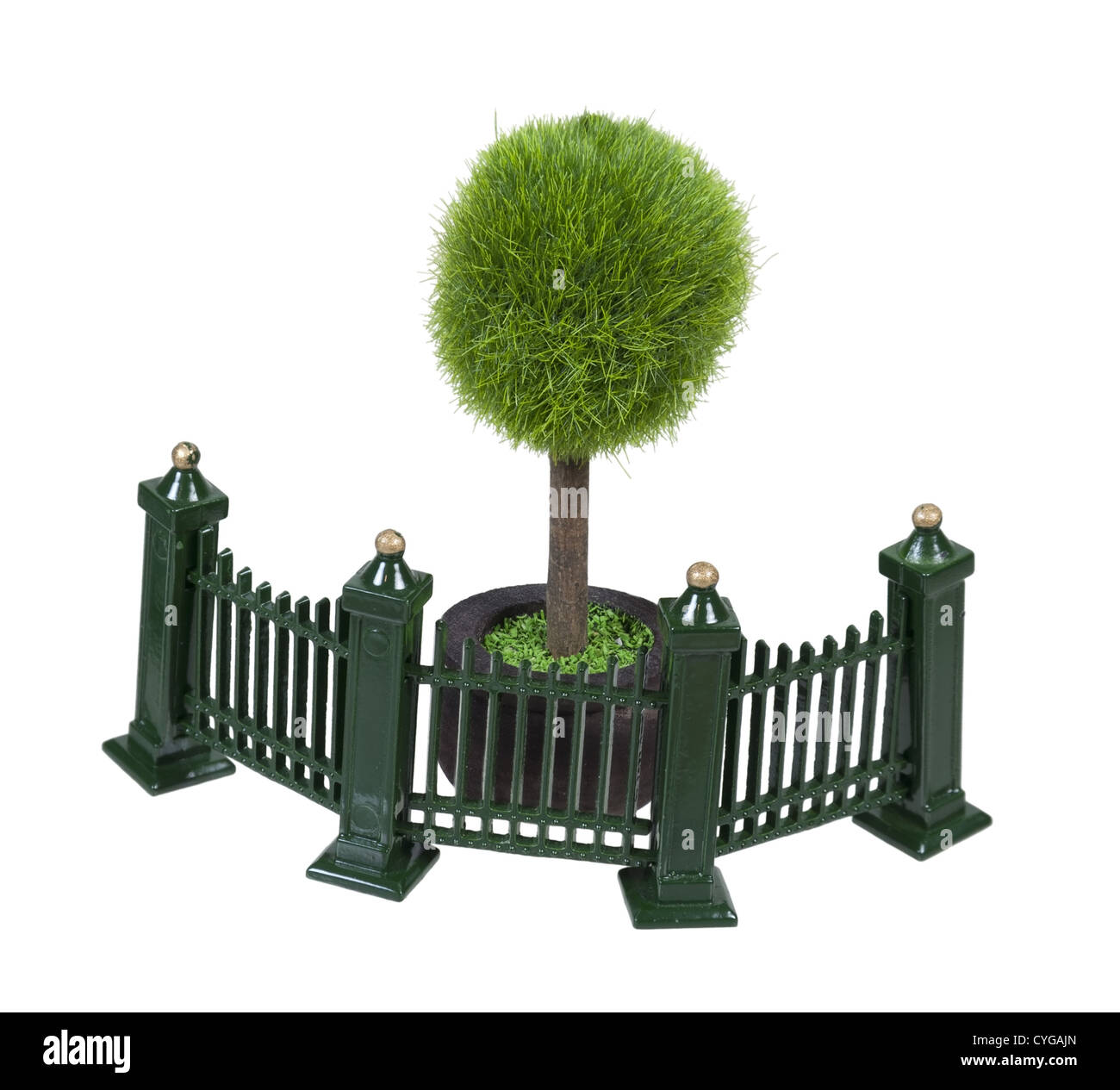 Metal fence with scrollwork painted green in front of a potted tree - Stock Image