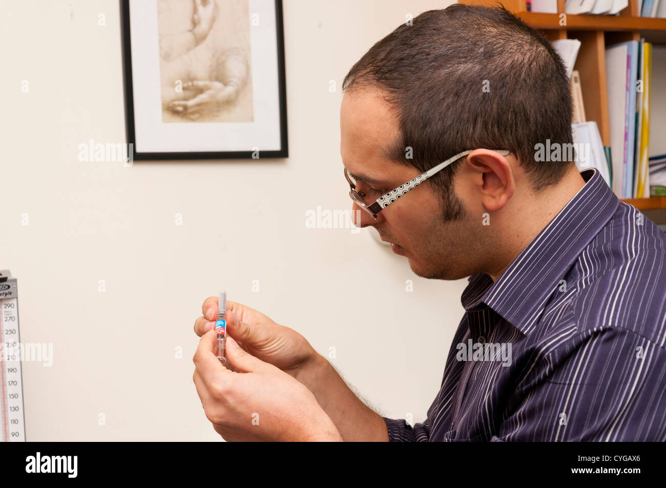 GP Doctor prepares flu jab vaccine. - Stock Image