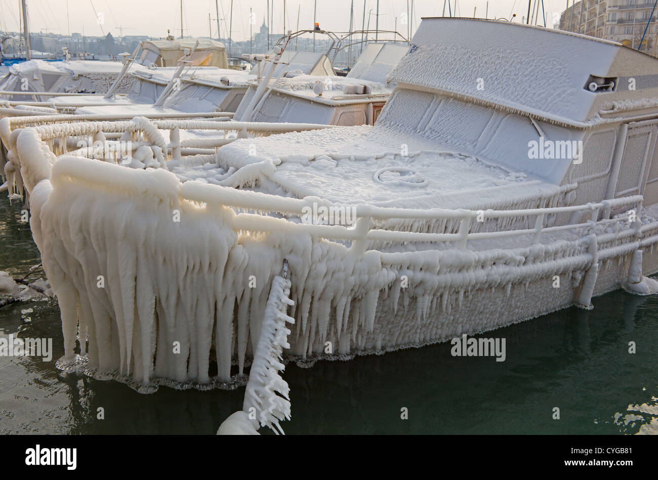 Motorboat frozen solid and full of ice in a harbour port at Geneva - Stock Image