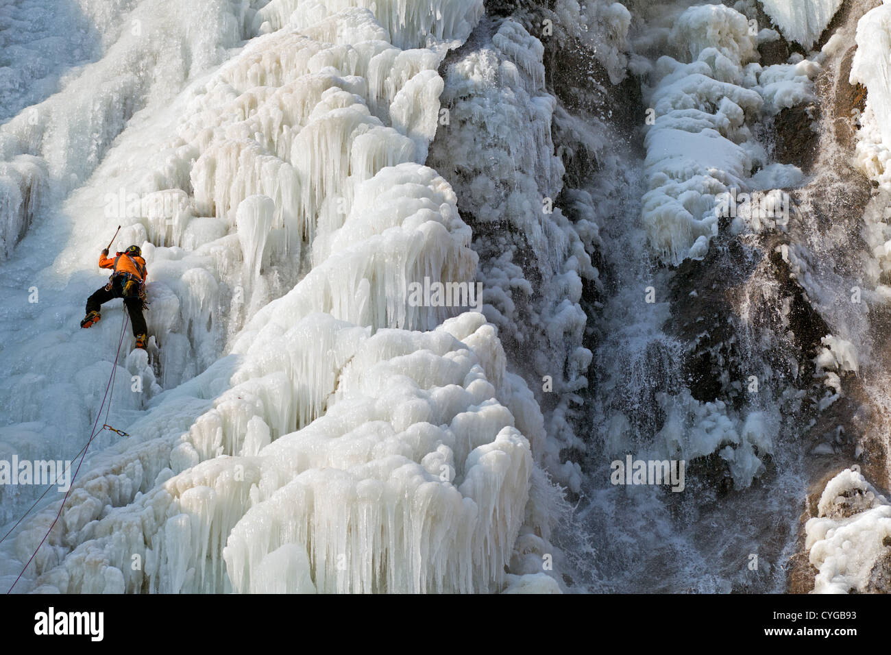 Ice climber in the frozen waterfall of Cascade de Pissevache Valais Wallis - Stock Image