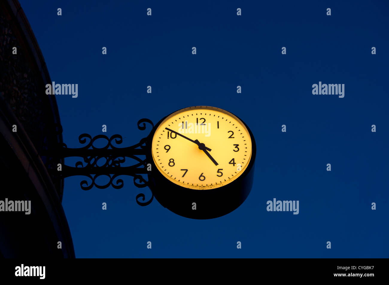 An ornate clock with an illuminated face on the side of a building in the night sky - Stock Image