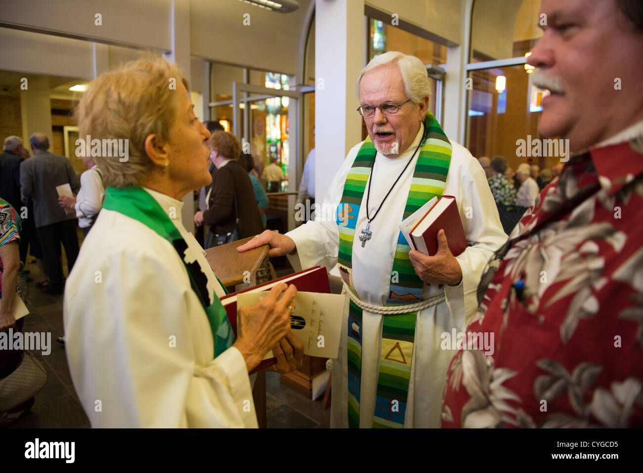 Pastors talk in narthax after service at St. Martin's Lutheran Church in Austin, Texas - Stock Image