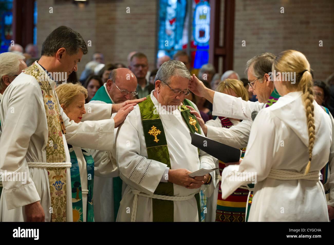 Fellow pastors bless Rev. Peder Sandager during his installation ceremony as senior pastor at St. Martin's Lutheran - Stock Image