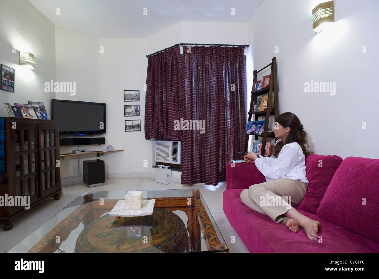 Woman Sitting On A Couch In A Living Room   Stock Image