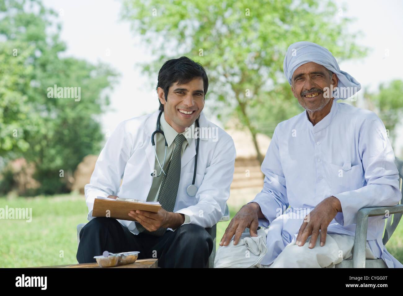 Doctor writing a prescription for a farmer - Stock Image