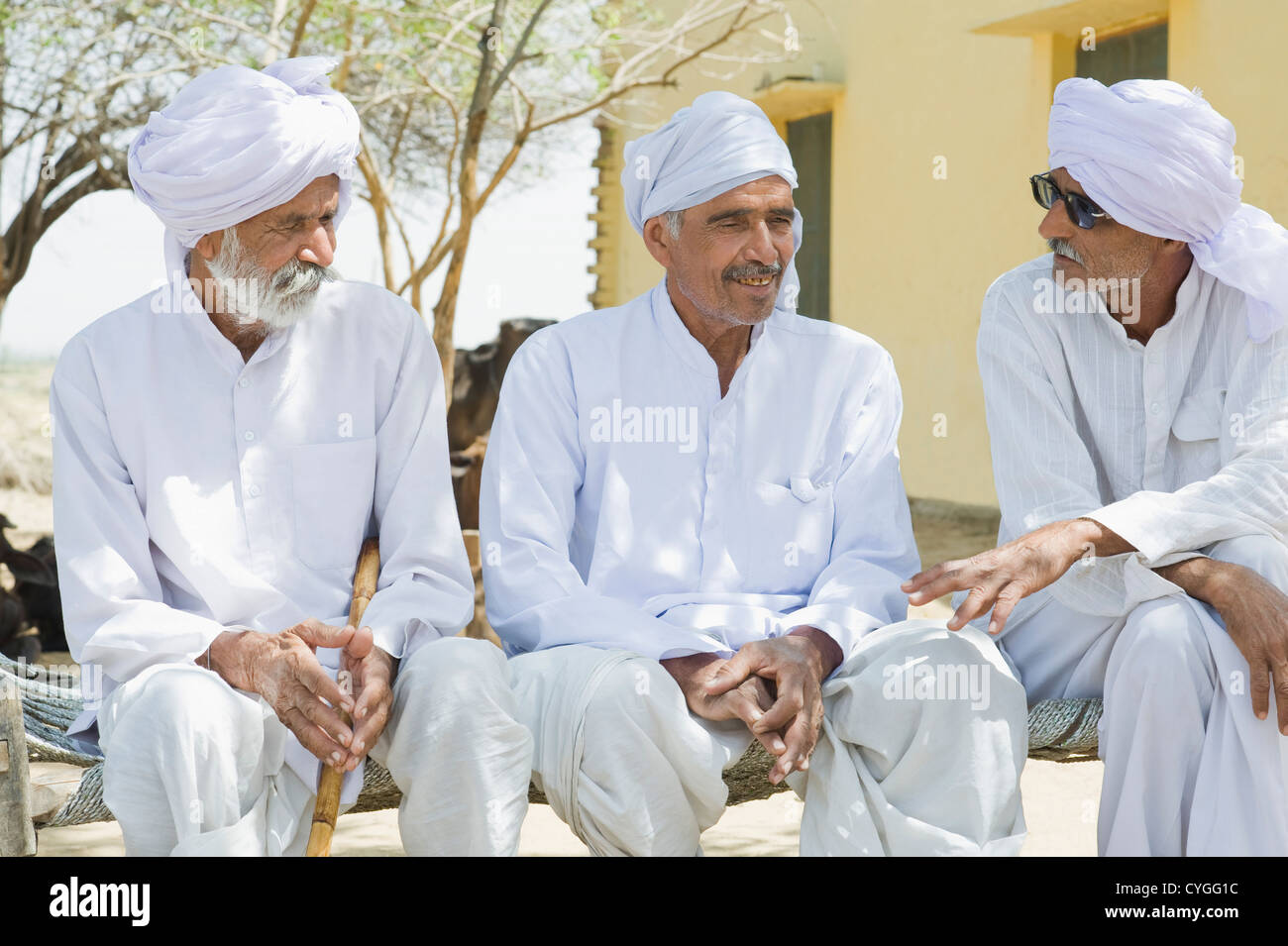 Three farmers sitting together and discussing - Stock Image