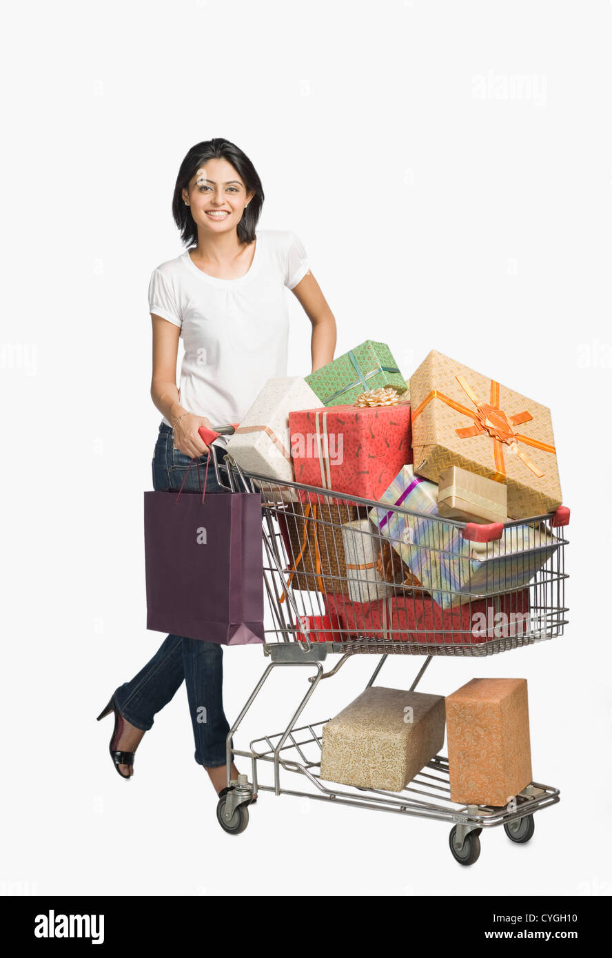 Woman pushing a shopping cart of gifts - Stock Image