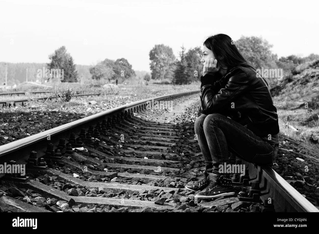 Depressed and lonely teenage girl with hands over her face sitting on the railroad stock
