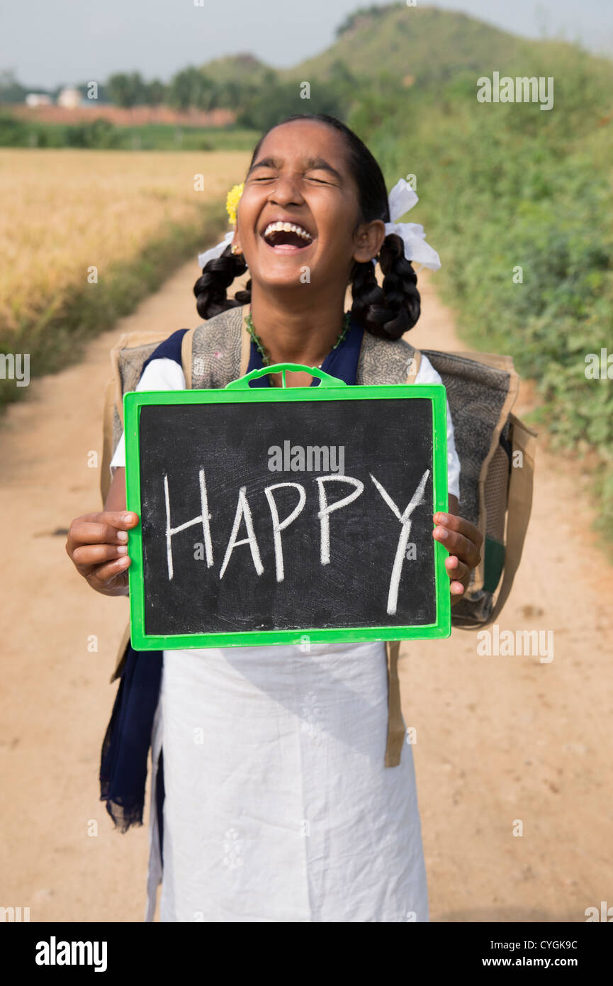 Laughing Indian school girl holding a chalkboard with happy written on it. Andhra Pradesh, India - Stock Image