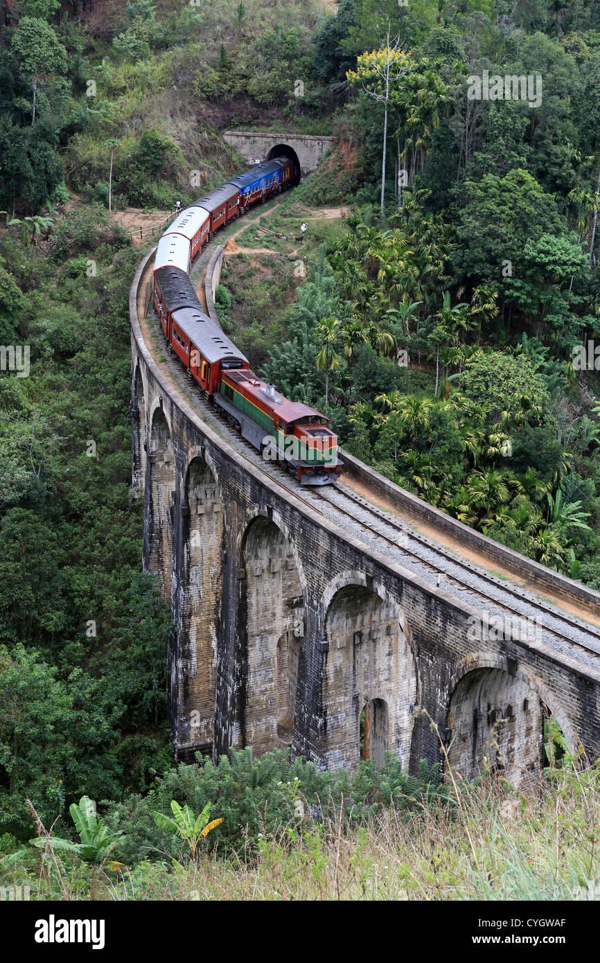 Commuter passenger train passing over Nine Arch bridge at Demorada in the Sri Lankan highlands. Stock Photo