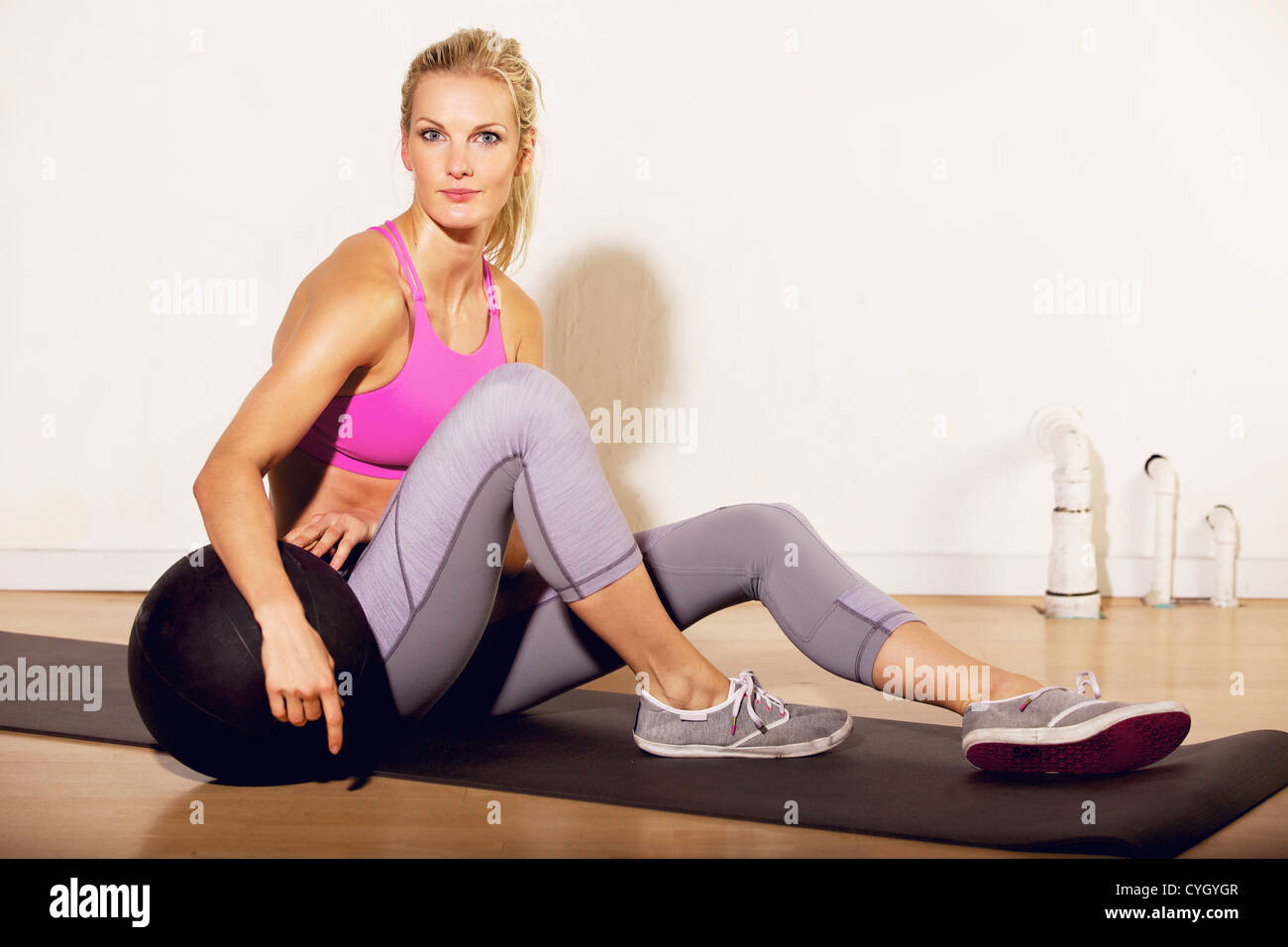 Fitness instructor at the gym sitting on the floor with a pilates ball Stock Photo