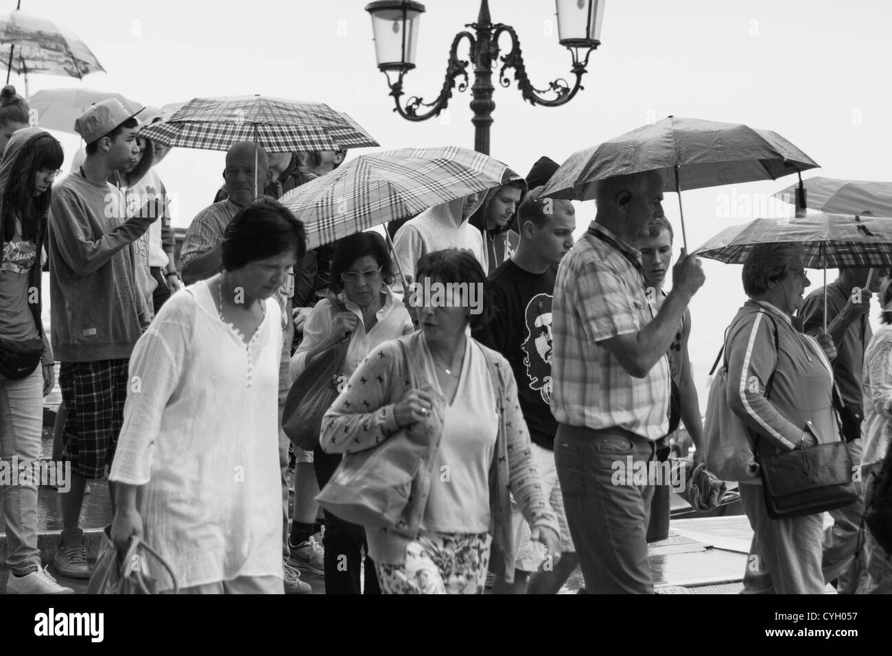 crowds of Tourists in the heavy rain. Venice waterfront.Italy - Stock Image