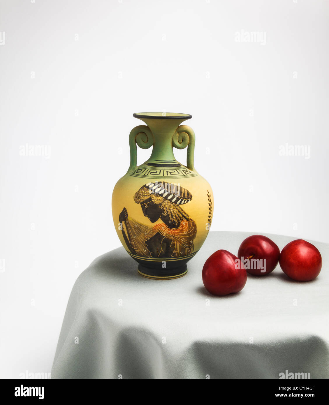 Greek Vase and red Plumes on round Table - Stock Image