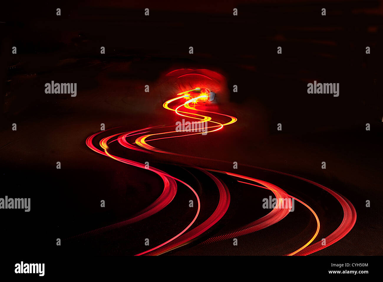 Car rear light trail on a country road at night. - Stock Image