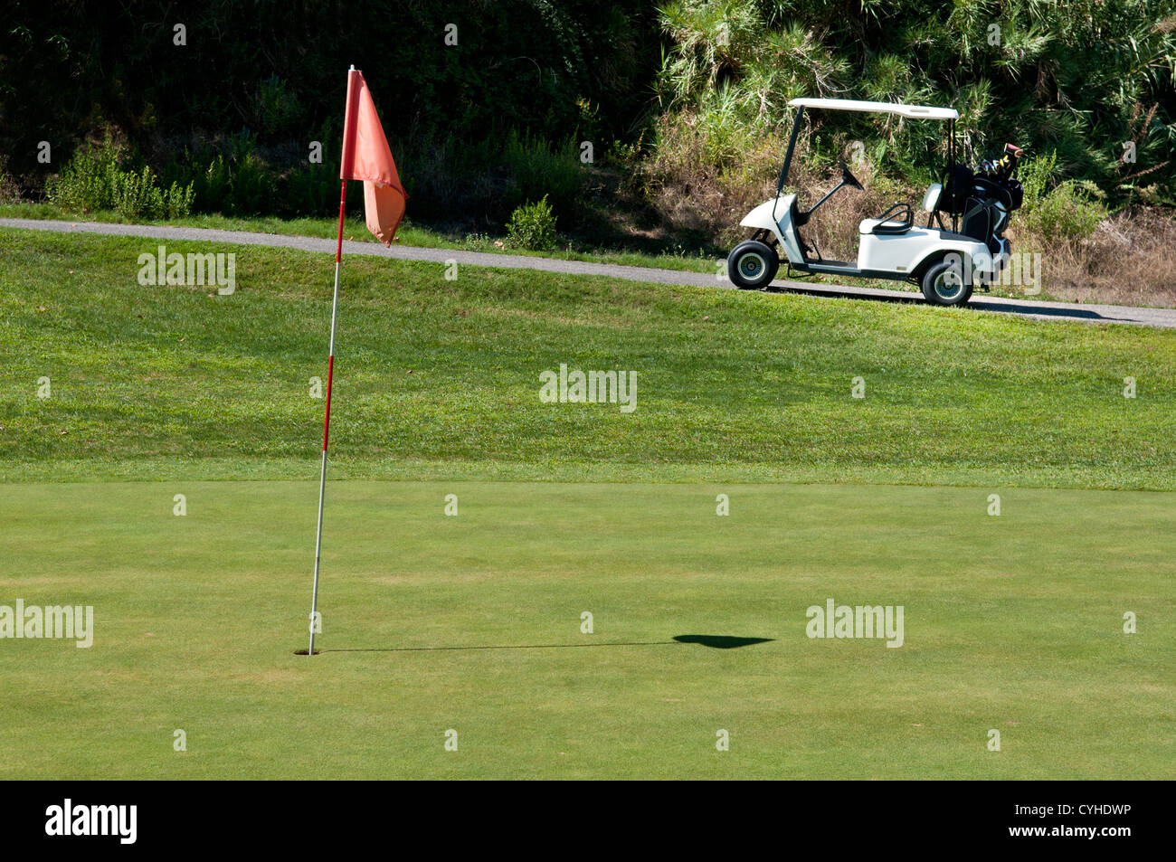 Golf cart next to a hole on a golf course - Stock Image