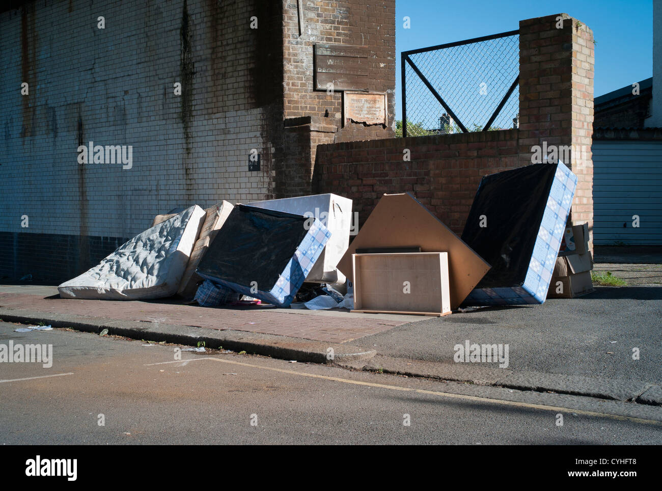 Fly tipping of old beds, and mattresses on pavement in Brent Cross, Golders Green, London. - Stock Image