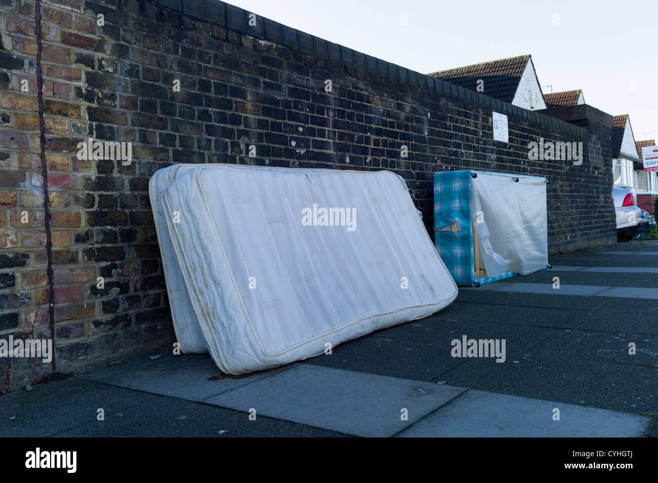 Fly tipping of old beds and mattresses on pavement in residential street in Brent Cross Golders Green, London - Stock Image