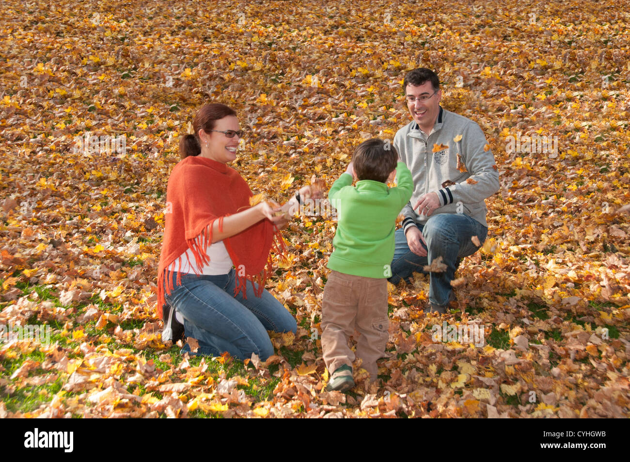 Parents and child playing autumn - Stock Image