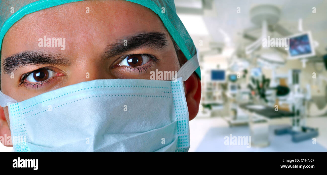 Closeup portrait of a surgeon with a operating room behind - Stock Image