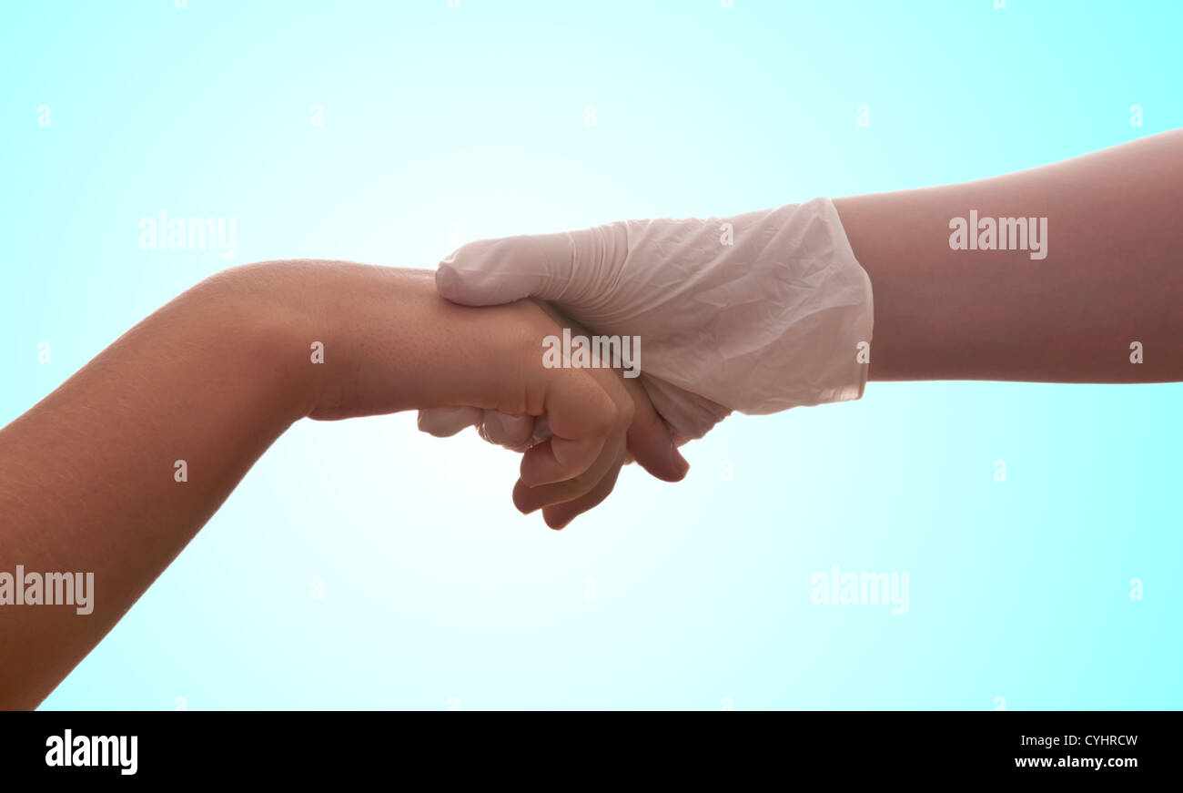 A hand with a medical latex glove holds another hand - Stock Image