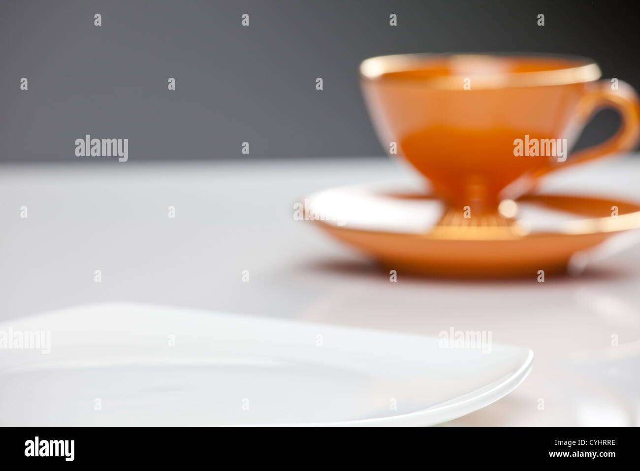 orange tea cup and white plate on reflective white surface. - Stock Image