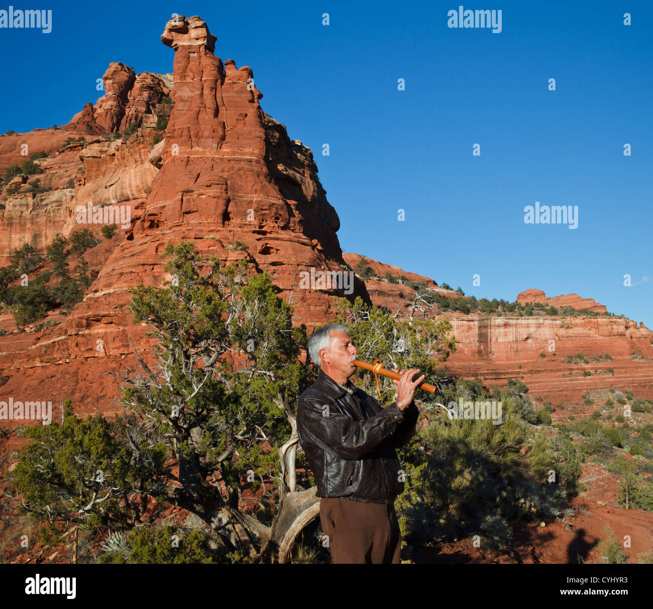 Arizona man plays Native American flute by Kachina Woman formation in Sedona, reached by hiking the Vista Trail - Stock Image