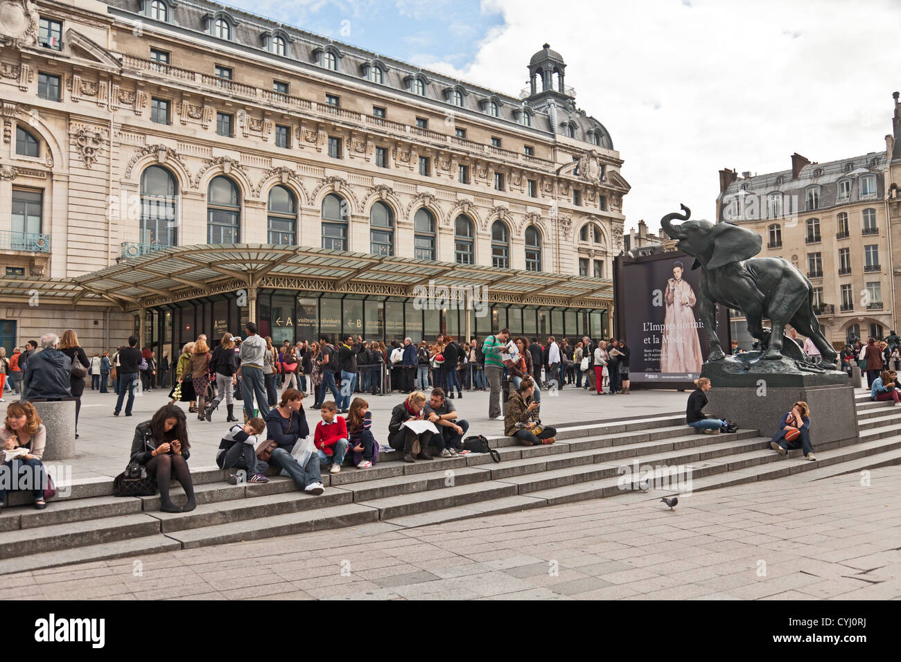 People queuing to enter a special exhibition - Musee D'Orsay, Paris. Other people relax on the steps. Frémiet's - Stock Image