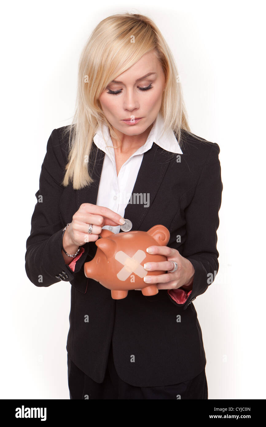Woman contemplates the unhealthy state of her finances as she places a single coin into a piggy bank with a plaster - Stock Image