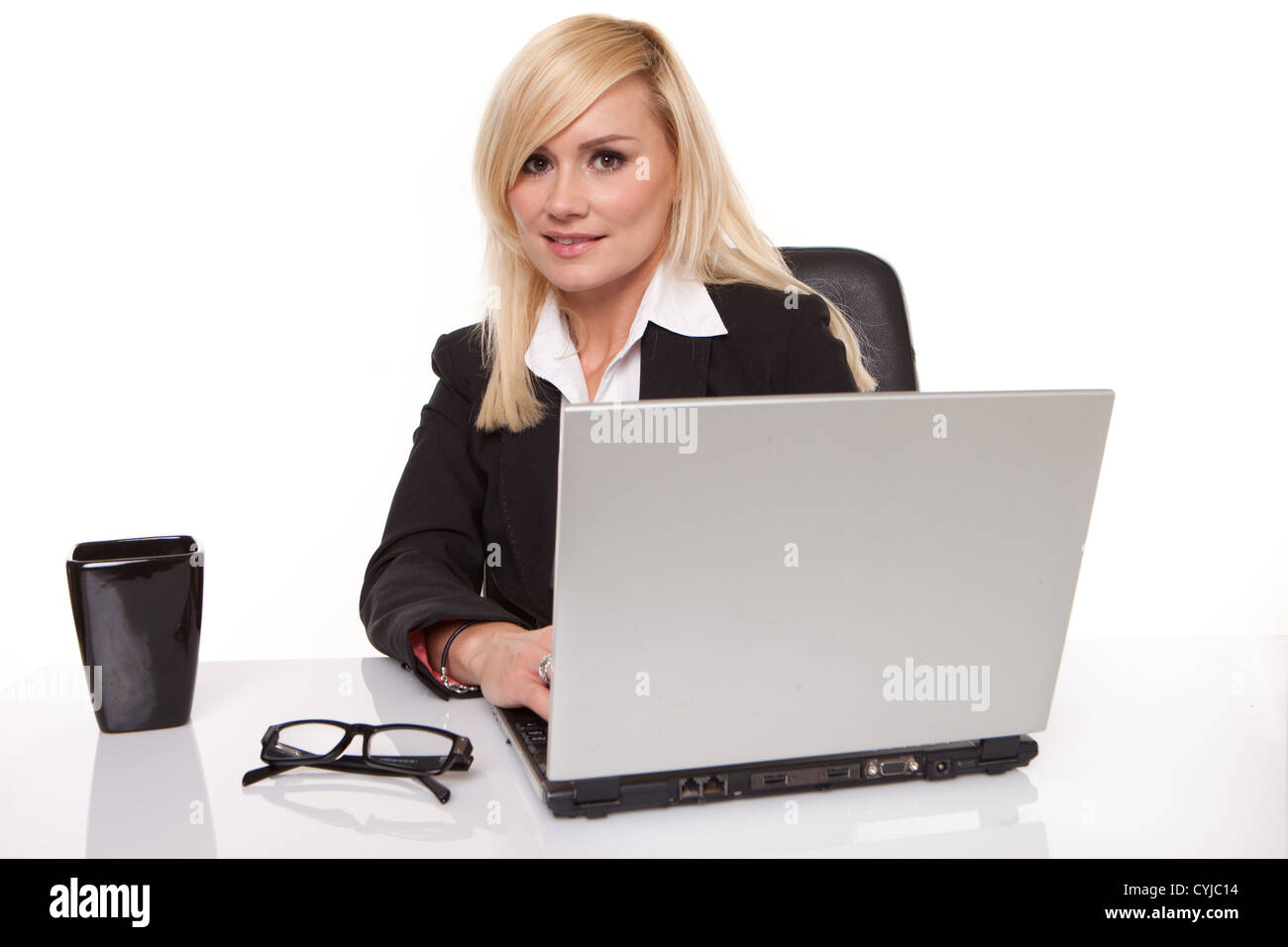 Efficient blonde businesswoman working on her laptop with her spectacles on the table alongside her - Stock Image
